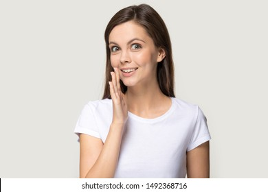 Smiling millennial girl in white t-shirt isolated on grey studio background look at camera tell secret private information, young woman whispering share sale promotion offer or deal, gossip or hearsay