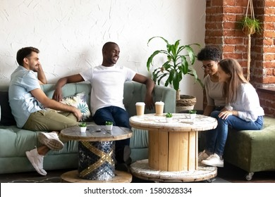 Smiling millennial girls talk get acquainted with multiracial young men hang out together in coffeeshop, happy multiethnic people sit in café have fun introducing chatting. Acquaintance concept