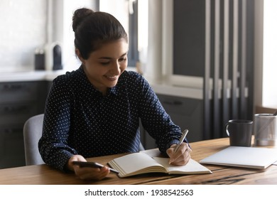Smiling millennial Indian female student write note in notebook working or studying online on smartphone. Happy young ethnic woman use cellphone make list or plan in paper notepad. Management concept.