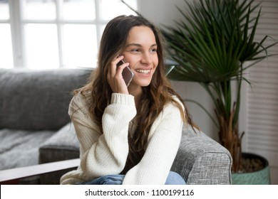 Smiling millennial mestizo woman talking on the phone at home, happy young girl holds cellphone making answering call, attractive teenager having pleasant conversation chatting by mobile with friend