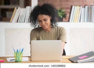 Smiling millennial woman sit at office desk work browsing internet at laptop, dreamy pensive african American female use computer typing chatting or surfing web, biracial girl busy studying online