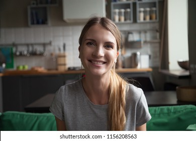 Smiling millennial woman sitting on kitchen sofa talking by videocall dating online looking at camera, video blogger vlogger recording vlog at home, lifestyle vlogging concept, head shot portrait