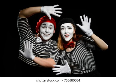 Smiling mimes in striped shirts. Man and woman, dressed as actors of pantomime theater, leaning on imaginary wall. Studio photo, black background.