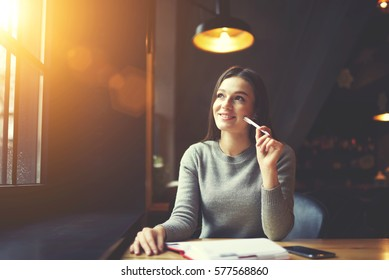 Smiling mindful female journalist working on creation book review planning to share impression after finishing reading novel with followers in social media while writing in notebook sitting in cafe