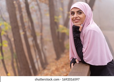 Smiling mirthful Muslim woman standing next to the banister in the park