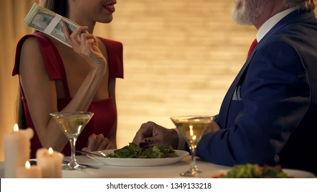 Smiling mistress holding money looking at senior man, marriage of convenience