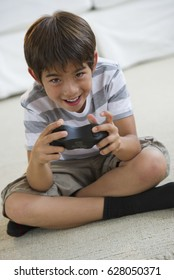 Smiling mixed race boy playing video game