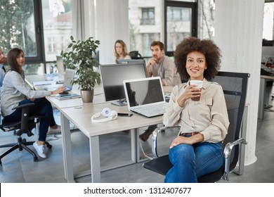 Smiling mixed race CEO sitting at office and drinking coffee while looking at camera. In background employees working.