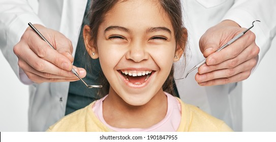 Smiling mixed race girl in a dental clinic for children. Child with a toothy smile during inspection of oral cavity by a dentist. Close-up