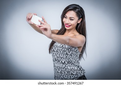 Smiling mixed race girl taking a selfie self portrait with smart phone in studio on plain background.