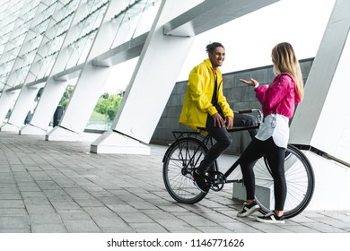 smiling mixed race man sitting on bike and talking to girlfriend at street