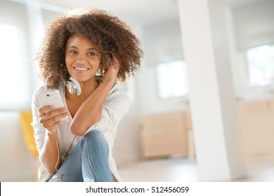 Smiling mixed-race girl sitting on floor at home and using phone