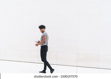 Smiling modern adult fit male curly ethnic in gray shirt and black jeans browsing smartphone while walking alone on street in front of white marble wall looking at camera