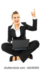 Smiling modern business woman got idea while sitting on floor with laptop
