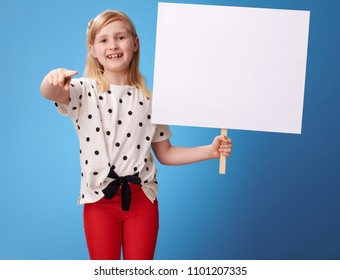 smiling modern child in red pants with blank poster pointing in camera isolated on blue background