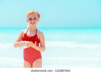 smiling modern child in red swimsuit on the seashore applying sun cream