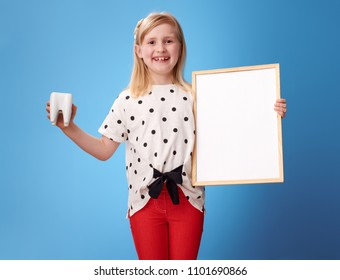 smiling modern girl in red pants showing tooth and blank billboard on blue background