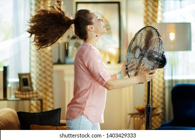 smiling modern housewife in the modern living room in sunny hot summer day enjoying fresh air in the front of working fan.