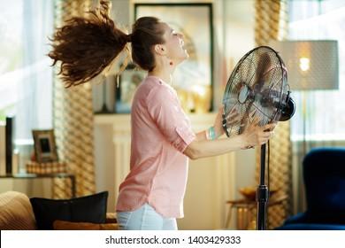 Die moderne Hausfrau im modernen Wohnzimmer in sonniger Hitze im Sommer genießt frische Luft vor dem Arbeitsventilator.