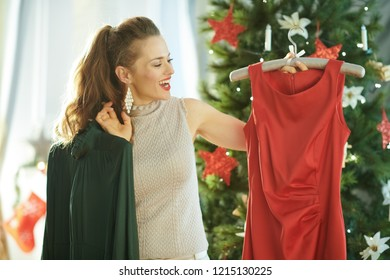 smiling modern housewife near Christmas tree selecting festive Christmas outfit