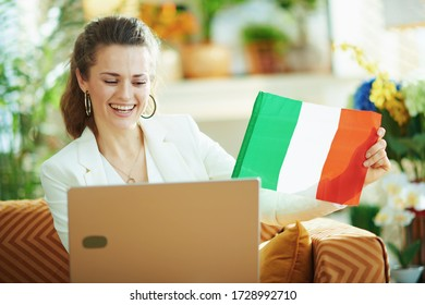 smiling modern middle age housewife in white blouse and jacket with laptop and Italian flag teaching foreign language in the modern house in sunny day.