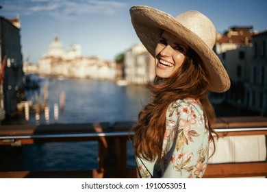 smiling modern middle aged traveller woman in floral dress with hat on Accademia bridge in Venice, Italy.