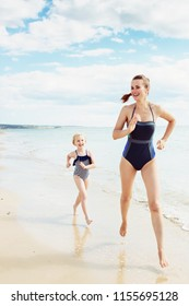 smiling modern mother and child in swimsuit on the beach running