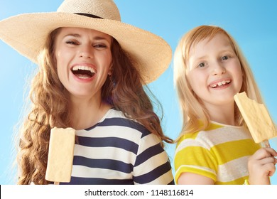 smiling modern mother and daughter with ice cream on a stick against blue sky