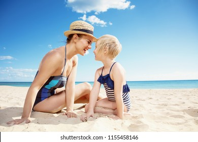 smiling modern mother and daughter in swimsuit on the seashore having fun time