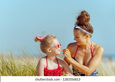 smiling modern mother and daughter in swimwear applying lipstick with spf on the ocean coast. lip balm with SPF sun protection to combat dry lips. Sun protected hair. minimal to no crowd peace.
