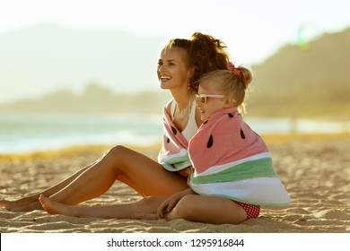 smiling modern mother and daughter in swimwear on the seashore in the evening looking into the distance wrapped in watermelon towel. activities for children. summer evening. blond hair young lady.