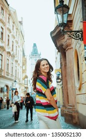 smiling modern solo traveller woman in colorful striped t-shirt at Staromestske namesti in Prague Czech Republic having walking tour.