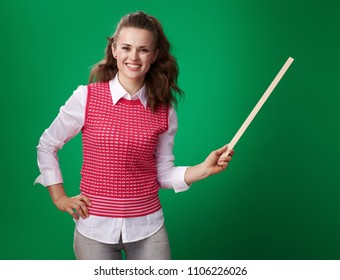 smiling modern student woman in a red waistcoat with a pointer isolated on green