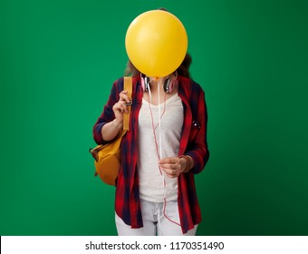 smiling modern student woman in a red shirt with backpack and headphones holding yellow balloon in the front of face isolated on green