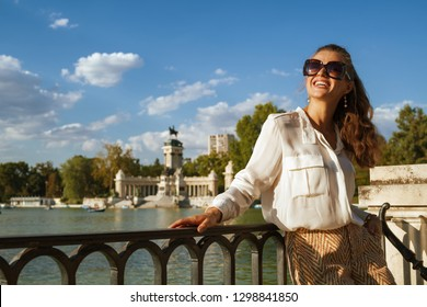 smiling modern tourist woman in white blouse and shorts at Parque del Buen Retiro in Madrid, Spain looking into the distance. having micro holidays. perfect destination choice. Sunny summer evening.