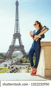 smiling modern traveller woman in blue jeans overall with coffee cup and two baguettes exploring attractions in Paris, France.