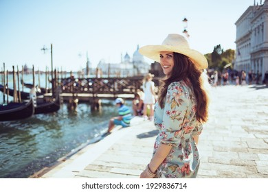 smiling modern traveller woman in floral dress with hat sightseeing on embankment in Venice, Italy.