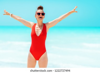 smiling modern woman in red swimsuit on the seashore rejoicing