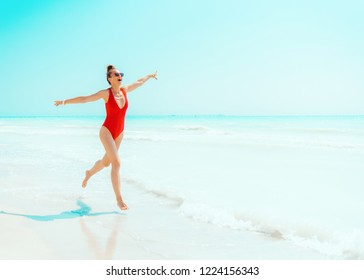 smiling modern woman in red swimwear on the seashore having fun time