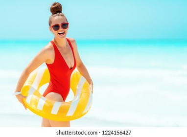 smiling modern woman in red swimwear on the seacoast wearing yellow inflatable lifebuoy