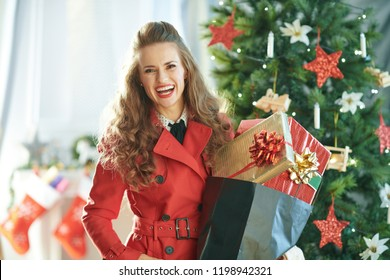 smiling modern woman in red trench coat with shopping bag full of Christmas present boxes near Christmas tree