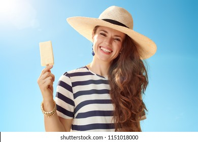 smiling modern woman in straw hat against blue sky with ice cream on a stick