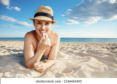 smiling modern woman in swimwear on the beach applying sun protection lipstick