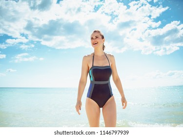 smiling modern woman in swimwear on the seashore looking into the distance