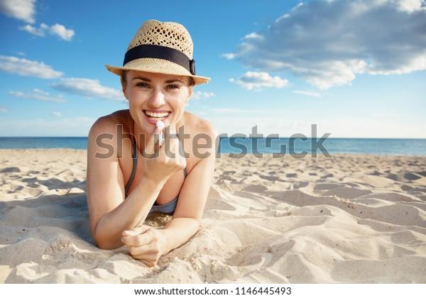smiling modern woman in swimwear on the beach applying sun protection lipstick