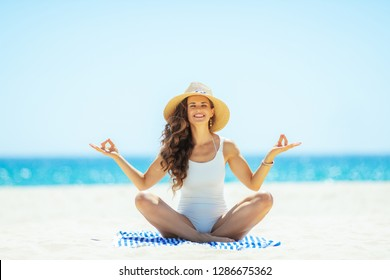 smiling modern woman in white swimsuit doing yoga while sitting on a striped towel on the seashore. woman in straw hat. Covering up with a hat to avoiding the harsh summer midday sun.