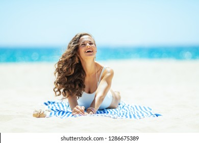 smiling modern woman in white swimsuit on the ocean shore lying on a striped towel enjoying. stressed free beach retreat. Sunny summer midday.