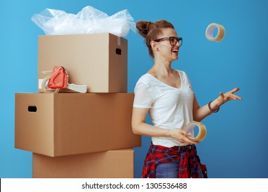 smiling modern woman in white t-shirt near cardboard box throwing up adhesive tapes isolated on blue