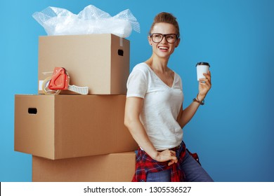 smiling modern woman in white t-shirt near cardboard box with coffee cup isolated on blue. Stress free moving.
