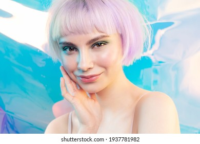 Smiling modern young blond girl with shiny glowing perfect facial skin. Cosmetology, dermatology and skincare concept. Cool teen fashion model with violet hair.